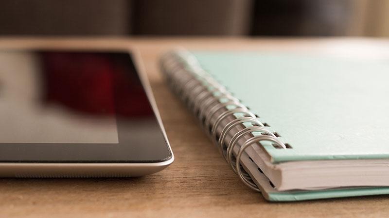 iPad et cahier, comparison de la réalité en stratégie digitale